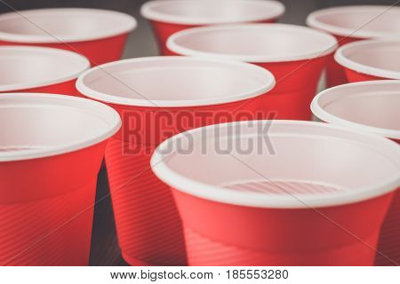 disposable plastic cups. red plastic cups on the wooden table. party plastic cups. a lot of plastic cups