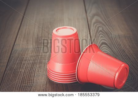 stack of disposable red plastic cups on the wooden table