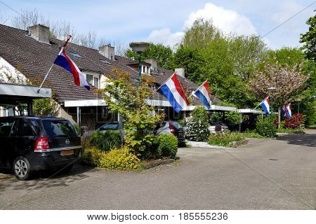 DRIEBERGEN THE NETHERLANDS - APRIL 27 2017: neighborhood in a dutch village with the dutch flag on kingsday