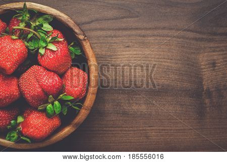 wooden bowl with strawberries. plate full of fresh strawberries on the brown table. raw strawberries on wooden background. fresh strawberries with copy space