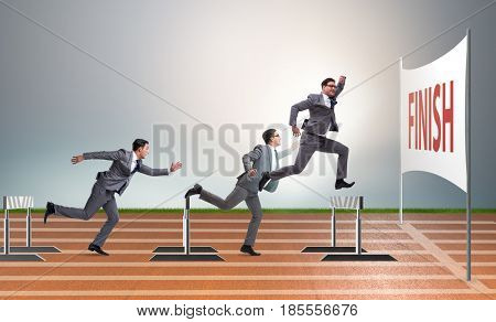 Businessman jumping over barriers in business concept