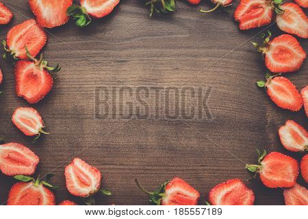 strawberries on the table. frame of strawberries on wooden background. many strawberries on brown wooden table with copy space. sliced fresh strawberries.