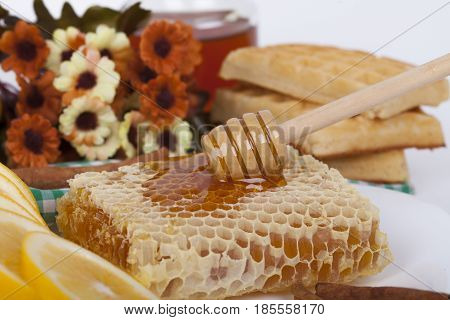 Close-up Honeycomb Topped With Honey And Dipper On A Table