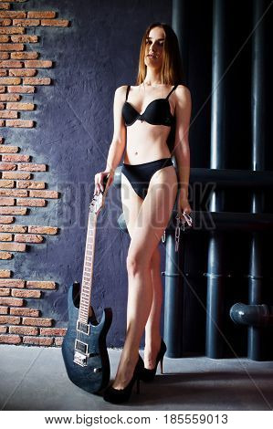 Portrait Of Sexy Brunette Girl At Black Underwear With Guitar At Industrial Background. Fashion Mode