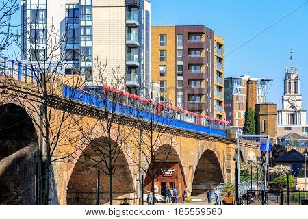 London UK - April 8 2017 - Limehouse viaduct with a Docklands Light Railway train passing by