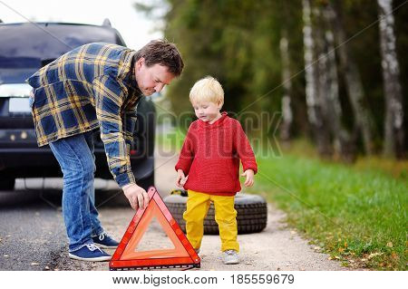 Father And His Little Son Repairing Car And Changing Wheel Together On Summer Day