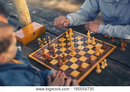 Active retired people old friends and free time two senior men having fun and playing chess at park spend time with grandson