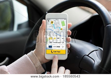 woman hands holding phone with app call taxi in the car
