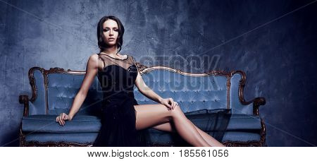 Beautiful and young woman posing in black dress on blue sofa. Vintage interior and retro background.