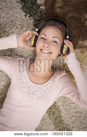Top view of a beautiful brunette lying on the carpet on the floor of her apartment listening to the music and enjoying her leisure time