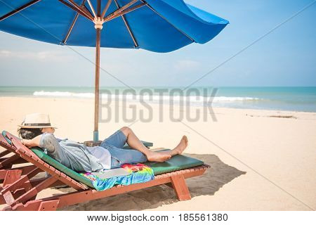 young man lying on wooden beach bench with blue umbrella and close his face by hat beautiful tropical beach island and blue sky vacation time and summer holiday concepts digital nomad lifestyle