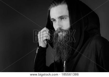 Portrait of handsome stylish serious man in a hood. Brutal man with a beard over black background.