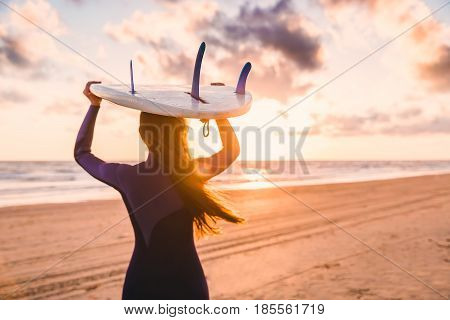 Beautiful young woman surfer girl with surfboard on a beach at sunset or sunrise. Surf girl and ocean
