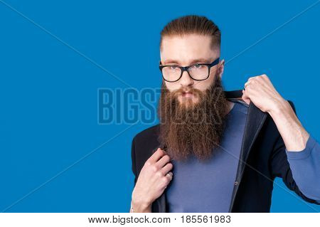 Taking life seriously. Portrait of handsome young man in formalwear adjusting his glasses while standing against grey background,