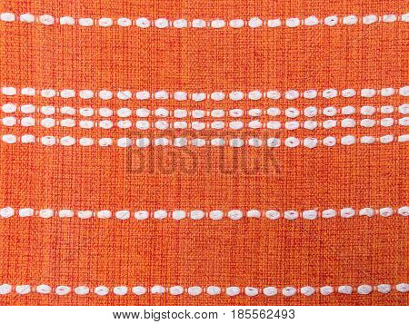 Close up of orange fabric pattern details with white dashed lines parallel