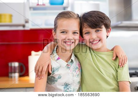 Portrait of siblings standing with arm around in kitchen at home