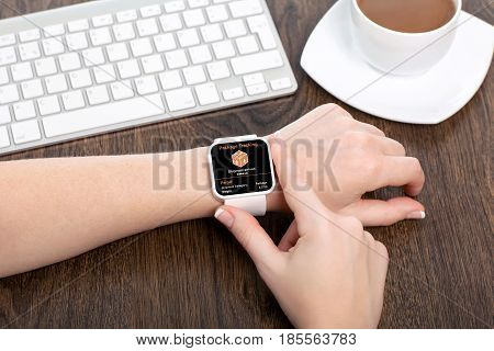 female hand with white smartwatch app package tracking on screen in office