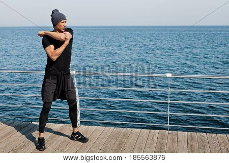 Side view of a person stretching an arm standing on the pier. Horizontal outdoors shot.