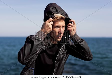 Horizontal outdoors shot of a man standing bu the ocean and adjusting the hood.