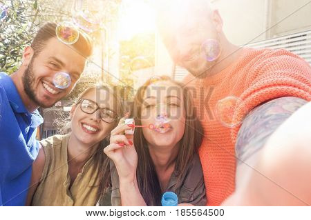 Happy friends taking snapshot selfie with mobile phone while throwing soap bubbles in camera - Young people having fun with new trends technology - Main focus on right woman eyes and near man face