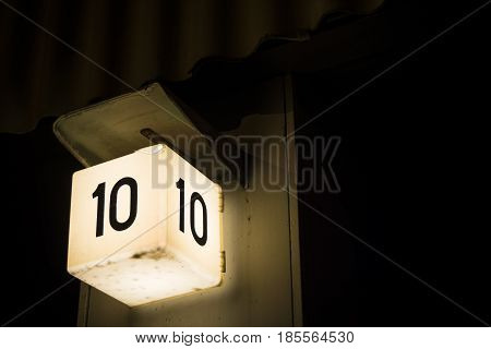 Bold number ten sign shining against large dark background