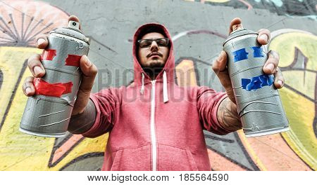 Young man drawing with two smiling sprays - Graffiti artist painting with aerosol color cans on the wall - Rebel and against system concept - Focus on bottles spray -