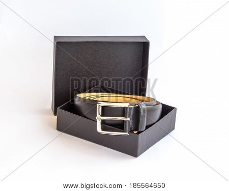 Black leather belt with metal buckle and its black cardboard packing box on a white background