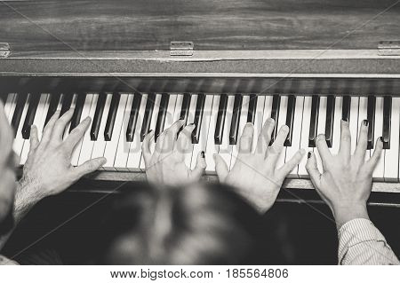 Young couple of artist playing piano together in a jazz bar - Artist performing in cocktail club - Black and white editing - Focus on center hands - Music and vintage retro concept
