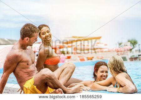 Happy friends swimming in pool on summer vacation - Young diverse culture people having fun laughing and relaxing together - Friendship and holidays concept - Focus on left guys faces - Warm filter