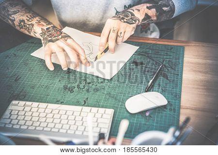 Tattoo artist cutting paper flower illustration inside ink studio - Hipster tattoer at work - New body skin trends generation - Contrast vintage filter with soft vignette - Focus on hands