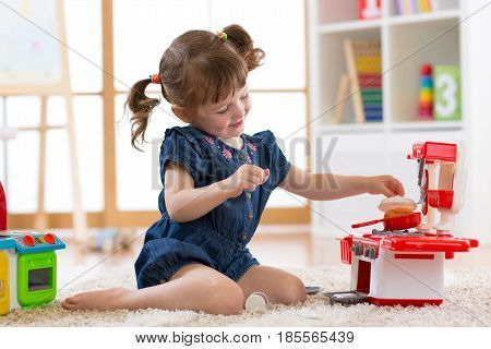 Little cute girl playing with utensil toys. Toddler kid in playroom. Kid sitting on floor and cook in toy kitchen.