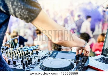 Dj mixing outdoor in after disco party on the beach - Disc jockey playing music with smoke colors and people dancing in background - Fest and event concept - Focus on thumb finger hand - Warm filter