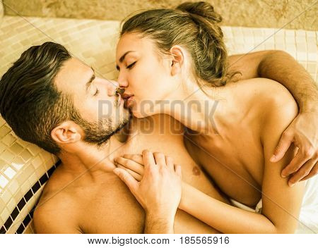 Young couple of lovers kissing in turkish steam room bath - Romantic love story on vacation resort hotel - Relationship concept with boyfriend and girlfriend together - Focus on man eye - Warm filter