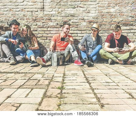 Group of trendy friends using mobile cell phones and listening music in old historical town center outdoor - Technology mania of new generation concept - Young people having fun - Warm contrast filter