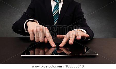 Businessman in suit typing with dark background