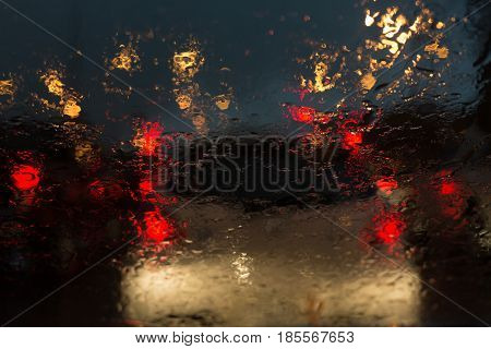 front view outside car traffic jam in heavy rainy day on city street at night abstract blur image defocused background