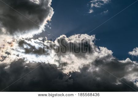Storm clouds and the clouds overshadow the sun. The sun's rays shining through the white clouds and dark blue clouds.
