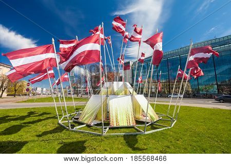 RIGA LATVIA - MAY 06 2017: View on the construction with waving national flags that is located in the city center of Riga.
