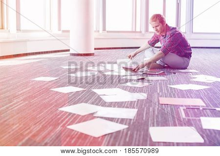 Businessman analyzing photographs while sitting on floor at creative office