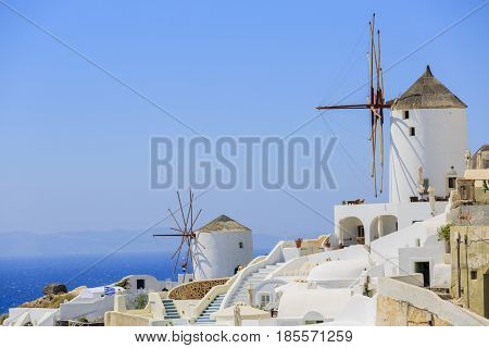 Picturesque view of Old Town of Oia on the island Santorini, white houses, windmills and church with blue domes, Greece