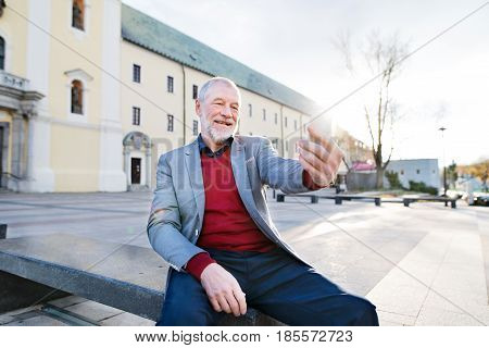 Handsome senior man in town sitting on bench, holding smart phone, taking selfie. Sunny spring day.