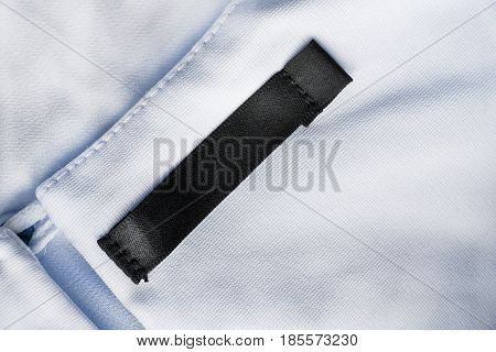Blank black clothes label on blue cloth as a background