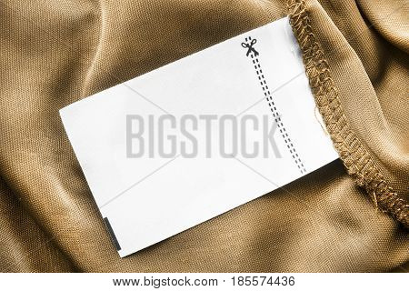 Blank white clothes label on yellow crumpled satin closeup