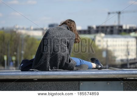 Moscow, Russia - May, 7, 2017: young woman sits on a bridge parapet in a center of Moscow