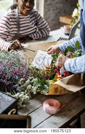 Florist Making Fresh Flowers Bouquet Arrangement with Best Wish Card