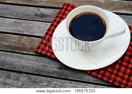 White cup of coffee on wooden background and copy space with red handkerchief