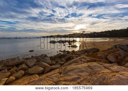 Evening sunset on Freycinet national park beach. Last sunlight reflecting on Coles Bay in East coast of Tasmania, Australia