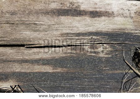Background of weathered wooden beam with withered grass in the corners