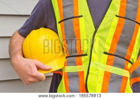 Closeup of man holding hardhat with house siding background.