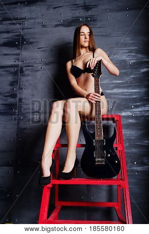 Portrait Of Sexy Brunette Girl At Black Underwear With Guitar Sitting On Red Ladder At Industrial Ba